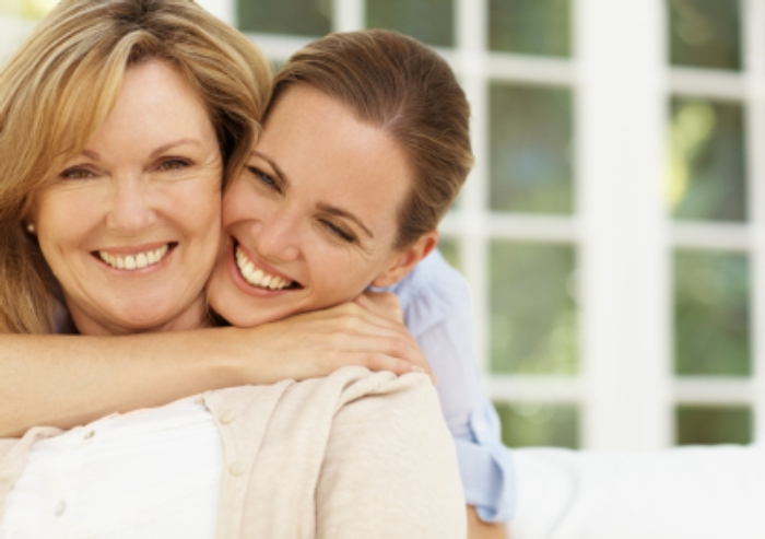 Smiling young woman embracing her mother - portrait
