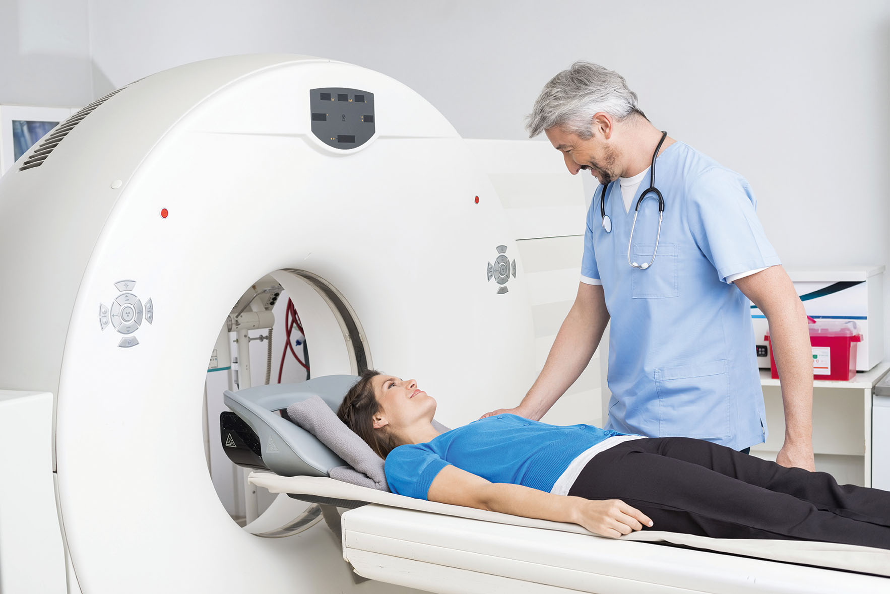 Smiling Doctor Talking To Patient Lying On CT Scan Machine